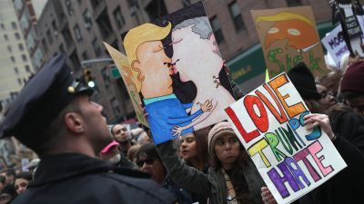 People hold up a drawing of Donald Trump and Vladimir Putin kissing during the Women's March on Jan. 21, 2017 in New York City. (Photo by John Moore/Getty Images)