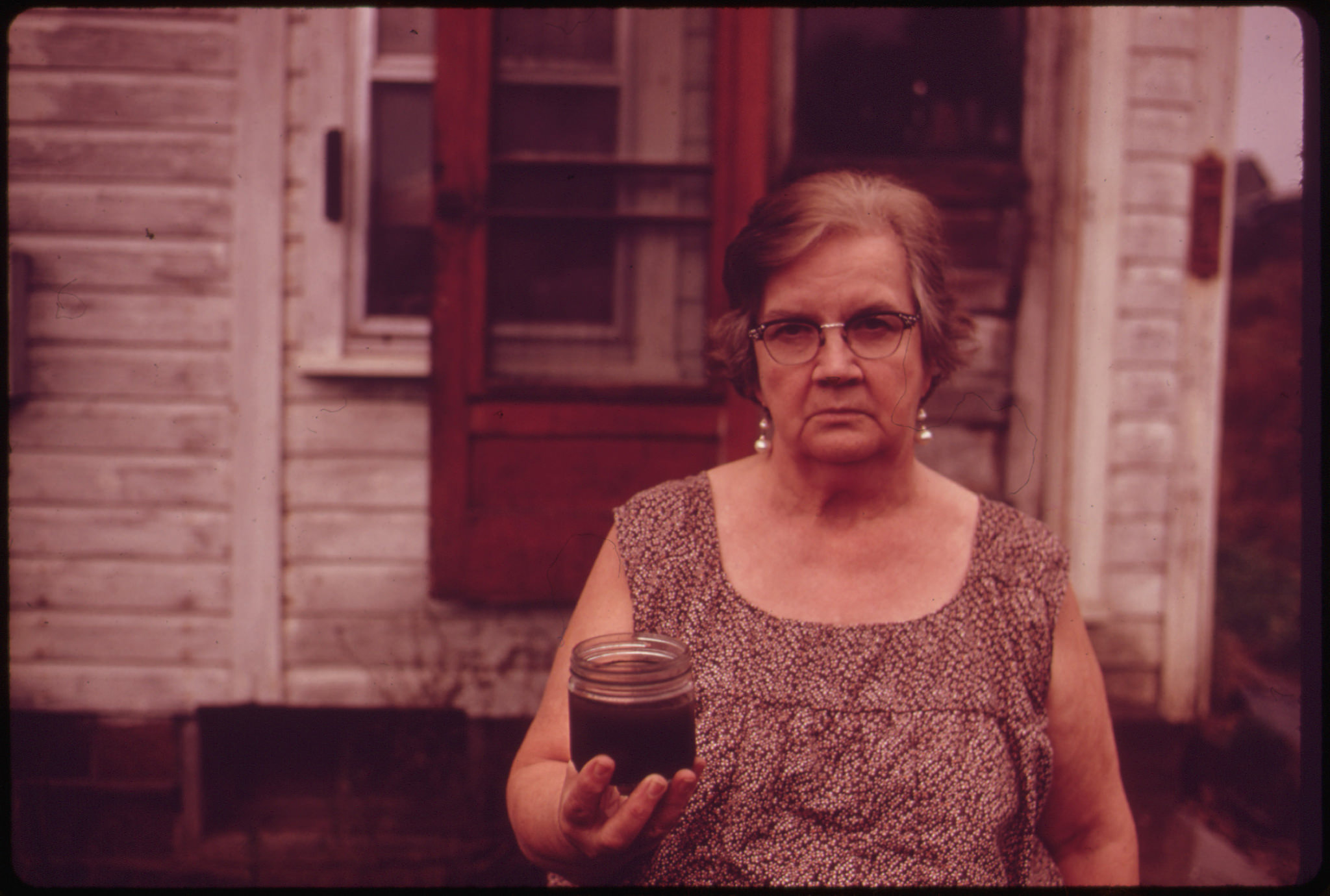 Mary Workman holds a jar of undrinkable water that came from her well, and filed a damage suit against the Hanna Coal Company, Steubenville (Jefferson County, Ohio), 1973. (Photo courtesy of the National Archives)
