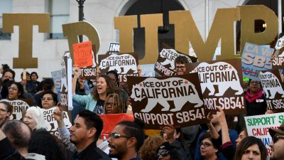 Migrant rights protesters demonstrate outside the Hall of Justice against the use of state police resources for federal immigration enforcement and deportation in Los Angeles on March 22, 2017. (Photo by Mark Ralston/AFP/Getty Images)