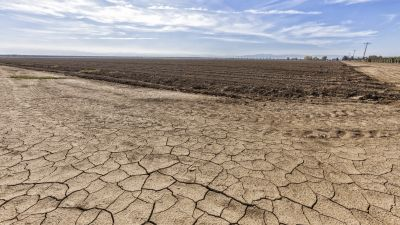 Cracked and dry earth next to fallow crop field in Fresno County, San Joachin Valley, California. (Photo by Citizens of the Planet/Education Images/UIG via Getty Images)