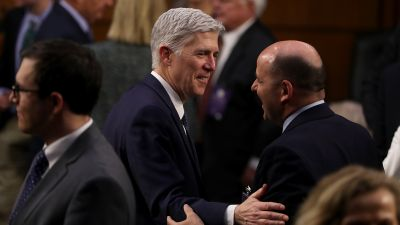 Judge Neil Gorsuch (left) greets an attendee during the third day of his Supreme Court confirmation hearing before the Senate Judiciary Committee in the Hart Senate Office Building, March 22, 2017 in Washington. (Photo by Justin Sullivan/Getty Images)