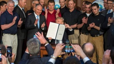 """Surrounded by miners from Rosebud Mining, President Donald Trump shows the signed Energy Independence executive order at the Environmental Protection Agency (EPA) headquarters in Washington, DC on March 28, 2017. Trump claimed an end to the """"war on coal"""" as he moved to roll back climate protections enacted by his predecessor, Barack Obama. (Photo by Jim Watson/AFP/Getty Images)"""
