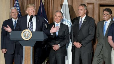 President Donald Trump speaks at EPA headquarters in Washington, DC on March 28, 2017 before signing an energy independence executive order as (from left) Vice President Mike Pence, EPA administrator Scott Pruitt, Secretary of the Interior Ryan Zinke and Secretary of Energy Rick Perry look on. (Photo by Ron Sachs/Pool via Bloomberg)