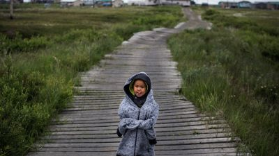 A Yupik child stands on one of the raised wooden sidewalks used to help cross unstable ground in Newtok, Alaska, on June 30, 2015. (Photo by Andrew Burton/Getty Images)