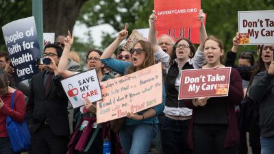 Protesters hold signs and shout at lawmakers walking out of the US Capitol in Washington, DC, on May 4, 2017 after the House of Representatives narrowly passed a Republican effort to repeal and replace Obamacare, delivering a welcome victory to President Donald Trump after early legislative stumbles. Following weeks of in-party feuding and mounting pressure from the White House, lawmakers voted 217 to 213 to pass a bill dismantling much of Barack Obama's Affordable Care Act and allowing US states to opt out of many of the law's key health benefit guarantees. (Photo by Nicholas Kamm/AFP/Getty Images)