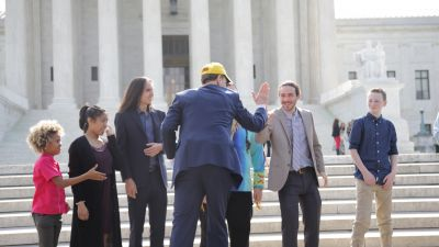 Sen. Ron Wyden (D-OR) high-fives one of the plaintiffs in Our Children's Trust's federal suit in April, 2017. (Photo by John Light/BillMoyers.com)