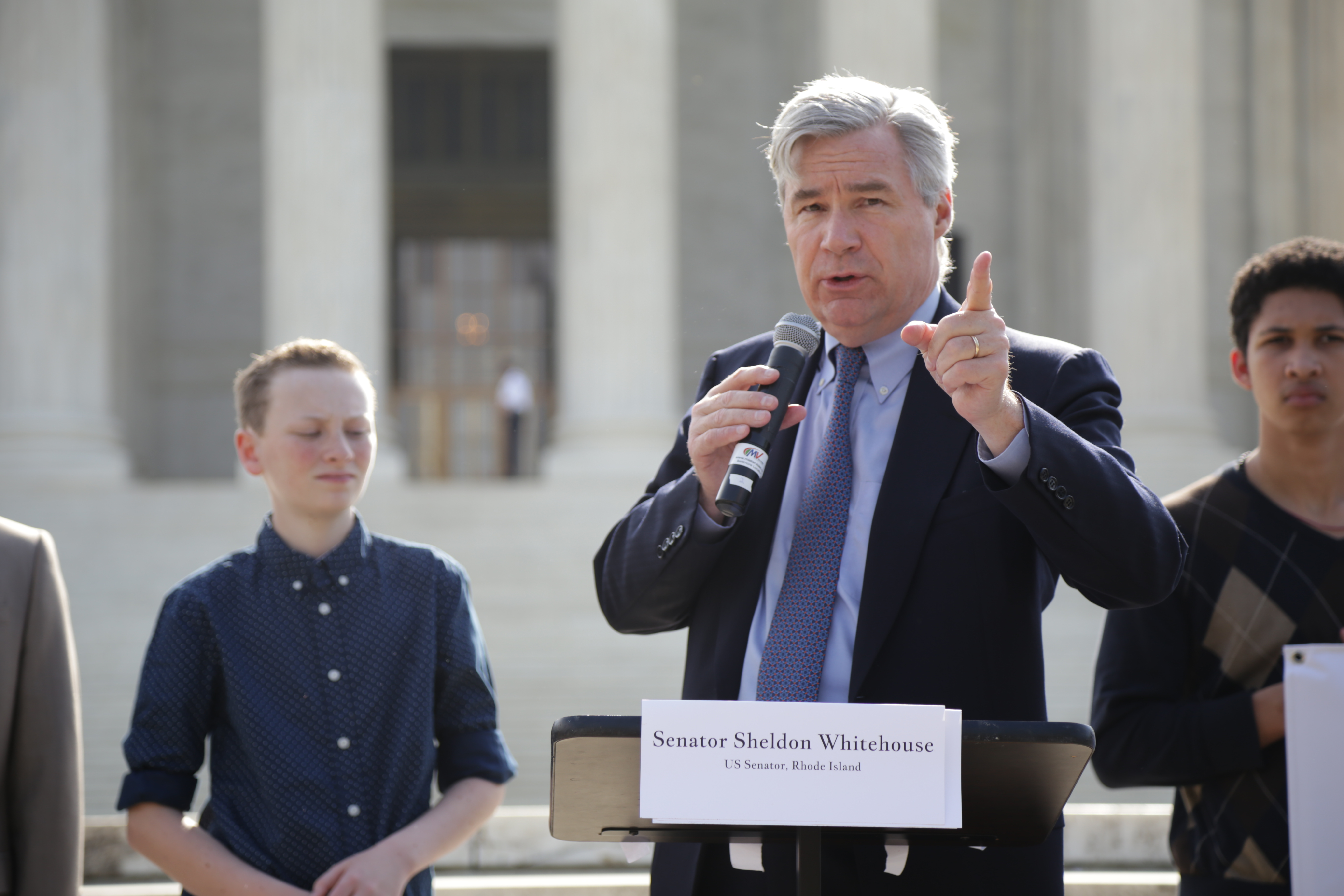 Sen. Sheldon Whitehouse (D-RI) points at the US Capitol Building while speaking in front of the Supreme Court. (Photo by John Light)