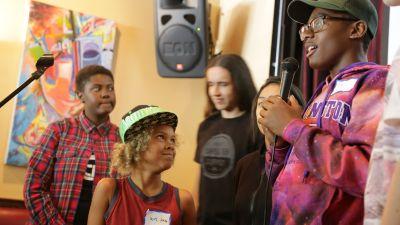 Plaintiff Levi Draheim, 9, listens as Isaac Vergun speaks during a presentation at Busboys and Poets, a restaurant in Washington, DC, in April 2017. (Photo by John Light)
