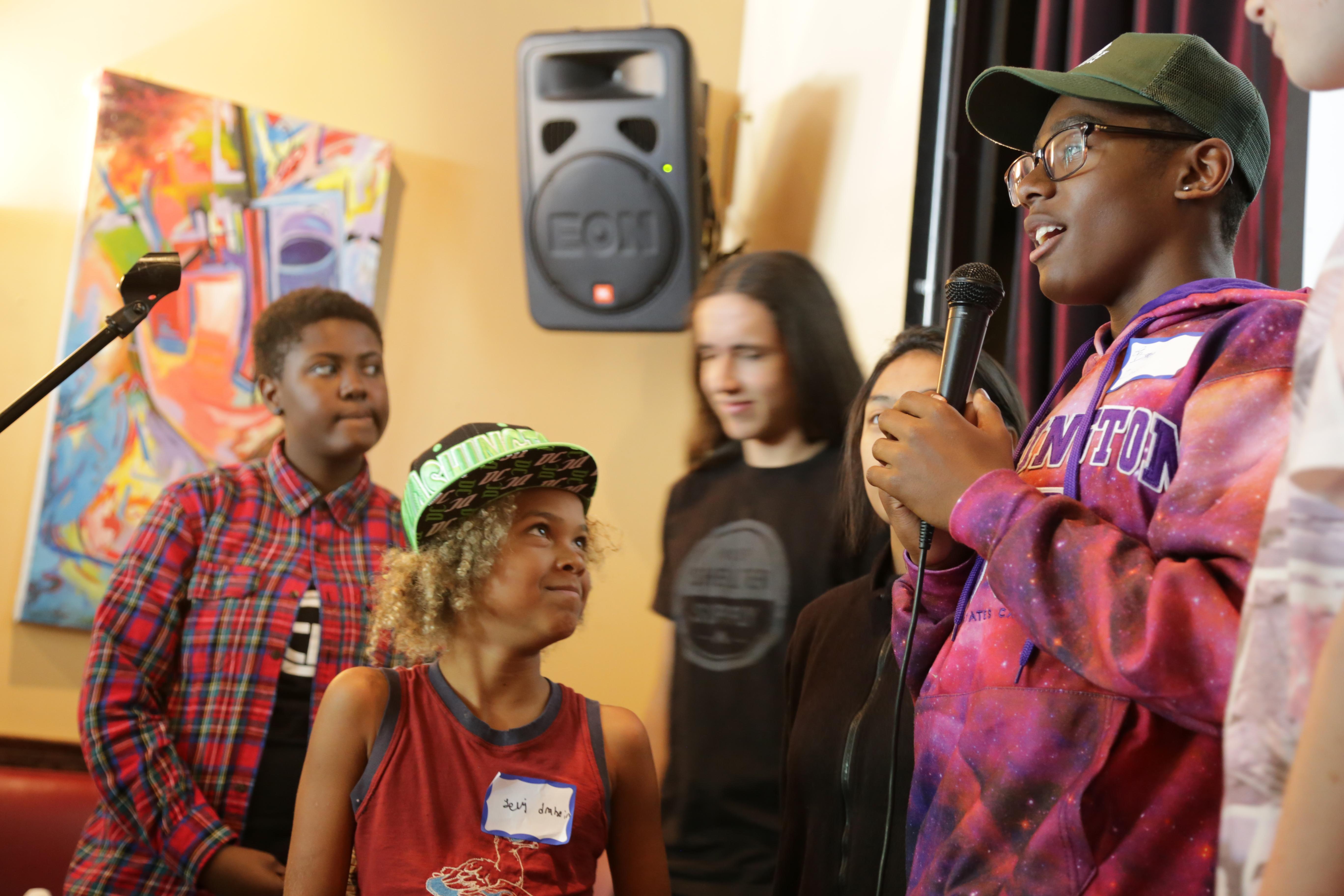 Plaintiff Levi Draheim (age 9) listens as Isaac Vergun (15) speaks during a presentation at Busboys and Poets, a restaurant in Washington, DC. (Photo by John Light)