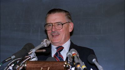 James Buchanan flashes a smile at a news conference in 1986 at George Mason University after it was announced that he is the winner of the Nobel Memorial Prize in economic science. (Photo by Don Emmert/AFP/Getty Images)