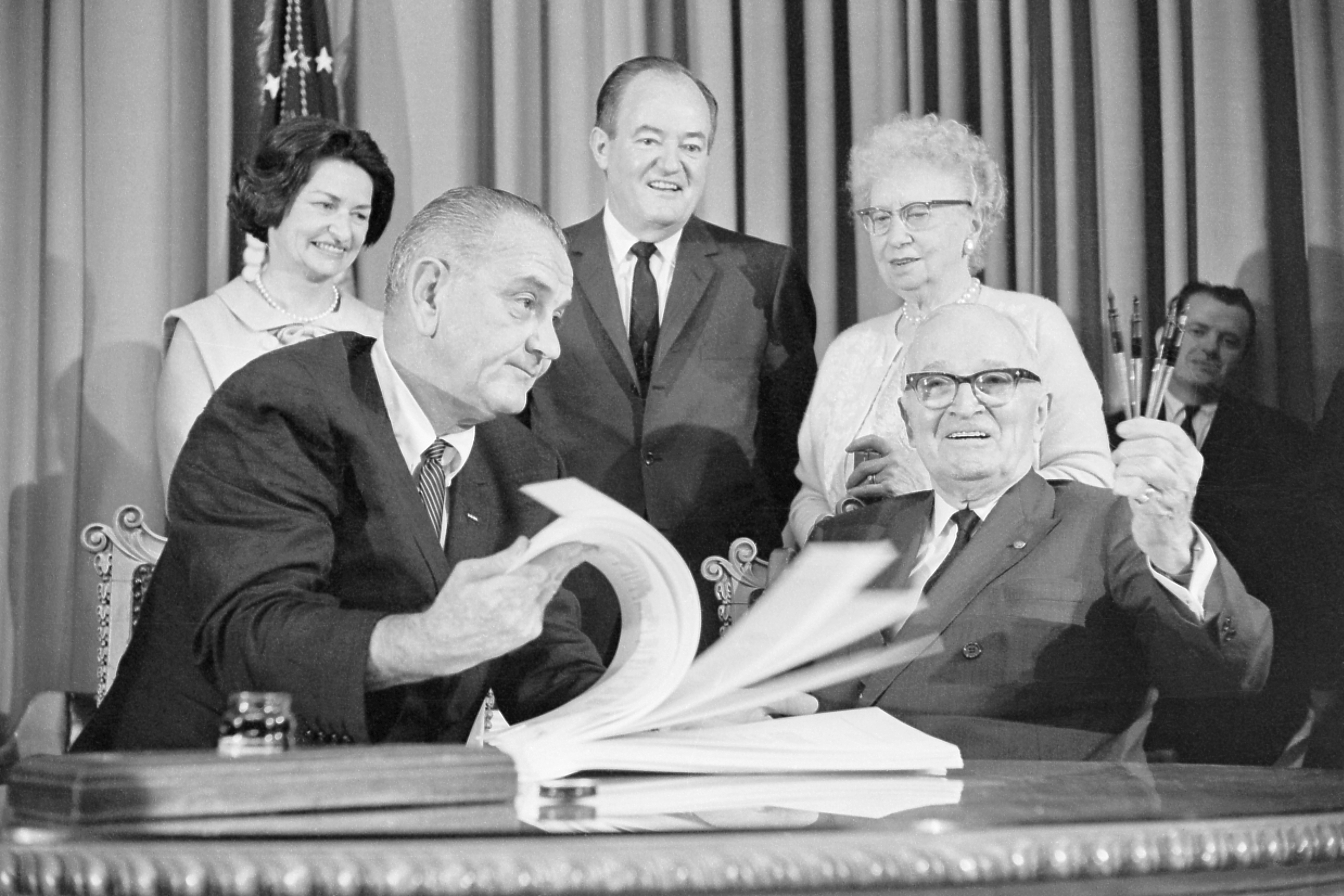 President Lyndon Johnson flips through the pages of the Medicare bill for former President Harry Truman in Independence, Missouri on July 30, 1965. Johnson flew to Independence to sign the bill in front of Truman, the man who originally proposed the legislation almost two decades before. Behind Johnson and Truman are Mrs. Johnson (left), Vice President Hubert Humphrey and Mrs. Truman. (Photo by Bettmann Collection via Getty Images)
