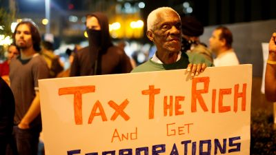 Demonstrator Randall Grey protests a taxation of the wealthy during a rally at Occupy Wall Street San Diego on Oct. 13, 2011 in San Diego, California. (Photo by Sandy Huffaker/Corbis via Getty Images)