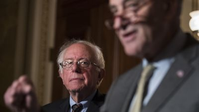 Sen. Bernie Sanders (I-VT) looks on as Senate Minority Leader Chuck Schumer (D-NY) speaks during a press conference to discuss legislation for a $15 minimum wage, on Capitol Hill on May 25, 2017. (Photo by Drew Angerer/Getty Images)