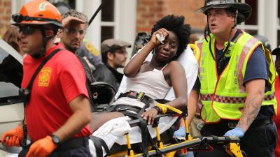 Rescue workers move victims on stretchers after car plowed through a crowd of counterdemonstrators marching through the downtown shopping district on Aug. 12, 2017 in Charlottesville, Virginia. (Photo by Chip Somodevilla/Getty Images)