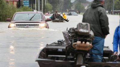 Rescue workers and volunteers help residents make their way out of a flooded neighborhood after it was inundated with rain water following Hurricane Harvey on Aug. 29, 2017 in Houston. This is what Texans were bracing for when Trump announced the military transgender ban and the Arpaio pardon four days earlier. (Photo by Scott Olson/Getty Images)