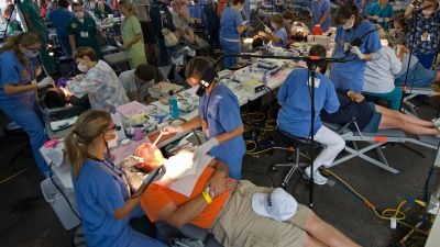 Hundreds of dentists and support staff work on patients inside the Virginia-Kentucky Fairgrounds in Wise, Virginia, on July 24, 2009 during the Remote Area Medical (RAM) Expedition. Close to 600 doctors and support staff volunteer their time for free treatment to individuals who have difficulty getting health care. (Photo by Paul J. Richards/AFP/Getty Images)
