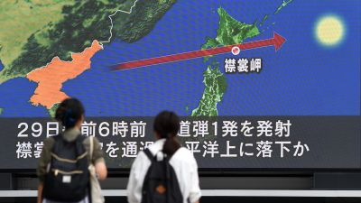 Pedestrians watch the news on a huge screen displaying a map of Japan and the Korean peninsula in Tokyo on Aug. 29, 2017, following a North Korean missile test that passed over Japan. (Photo by Toshifumi Kitamura/AFP/Getty Images)