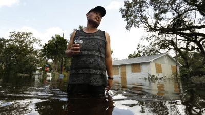 Gilberto Diaz, 42, stands in 4 feet of water in his neighborhood of Bonita Springs, Florida. Originally from Guatemala, he has lived in Florida since 1994. (Photo by Carolyn Cole/Los Angeles Times via Getty Images)