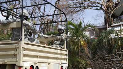 Members of the US military ride in a truck down a main street in the Cruz Bay section of St. John in the US Virgin Islands on Sept. 12, 2017. The island was hit hard by Hurricane Irma. (Photo by Jessica Rinaldi/The Boston Globe via Getty Images)