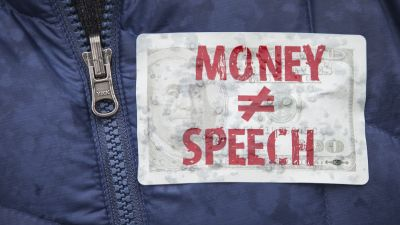 An attendee wears a sticker against money in politics during a rally calling for an end to corporate money in politics and to mark the fifth anniversary of the Supreme Court's Citizens United decision in Washington, DC, on Jan. 21, 2015. (Photo by Drew Angerer/Getty Images)
