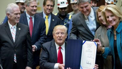 """President Donald Trump signs H.J. Res. 38, disapproving the rule submitted by the US Department of the Interior known as the Stream Protection Rule in the Roosevelt Room of the White House on Feb. 16, 2017. The Department of Interior's Stream Protection Rule, which was signed during the final month of the Obama administration, """"addresses the impacts of surface coal mining operations on surface water, groundwater, and the productivity of mining operation sites,"""" according to the Congress.gov summary of the resolution. (Photo by Ron Sachs-Pool/Getty Images)"""