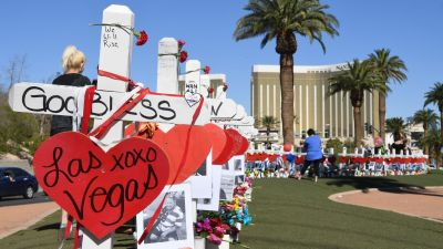 """Mourners gather at the """"Welcome to Las Vegas"""" sign where Greg Zanis, a retired carpenter from Chicago, placed 58 crosses to honor those who were killed during the Route 91 Harvest country music festival shootings in Las Vegas on Oct. 6, 2017. (Photo by Denise Truscello/Getty Images)"""