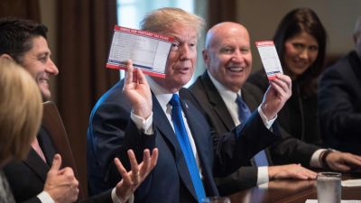 President Donald Trump shows samples of the proposed new tax form as he meets with House Republican leaders and Republican members of the House Ways and Means Committee at the White House in Washington, DC, on Nov. 2, 2017. (Photo by Nicholas Kamm/AFP/Getty Images)