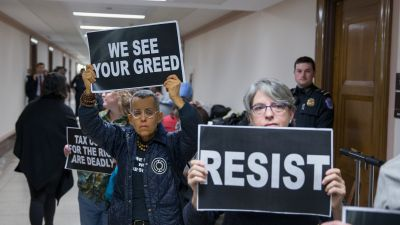 Protesters demonstrate near the full Senate Budget Committee markup of the tax reform legislation on Capitol Hill on Nov. 28, 2017 in Washington, DC. Republicans in the Senate hope to pass their legislation this week and work with the House of Representatives to get a bill to President Donald Trump before Christmas. (Photo by Tasos Katopodis/Getty Images)
