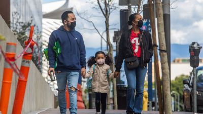 A family walks wearing masks in Downtown Los Angeles on March 22, 2020, during the coronavirus (COVID-19) outbreak. (Photo by APU GOMES/AFP via Getty Images)
