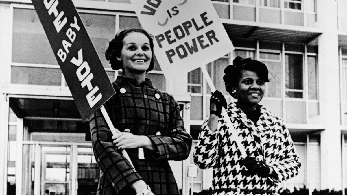 "Two smiling women stand outdoors and hold signs reading ""Vote Baby Vote"" and ""Voting is People Power,"" c. 1970. (Photo by Gabriel Hackett /Getty Images)"