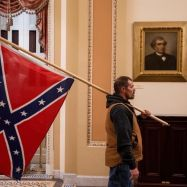 A member of the mob involved in the insurrection at the US Capitol on Wednesday, Jan. 6, 2021, holds a Confederate flag. (Twitter)
